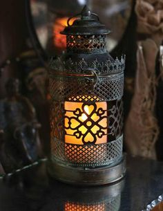 The buttery light of a faux pillar candle filters through ornate verdigris metalwork.