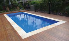Small Palladium Plunge Fiberglass Pool with Natural stone coping surrounded by a wooden deck.