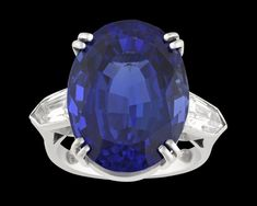 Tanzanite and Diamond Ring, 22.00 Carats~ Possessing an entrancing deep violet-blue hue, an extraordinary 22.00-carat tanzanite is elegantly displayed in this ring. The oval-shaped jewel is perfectly accented by two nearly colorless shield step-cut white diamonds totaling approximately 1.00 carat, adding sparkle to this stylish creation. ~M.S. Rau Tanzanite Jewelry, Rare Gemstones, Alexandrite, White Diamonds, Peridot, Hue, Garnet, Sparkle, White Gold