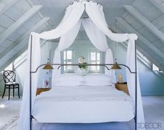 A dreamy canopy bed and rustic whitewashed floors are a match made in heaven in this beach bedroom from Elle Decor.