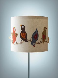 felt shapes and designs on a lampshade. what an easy transformation for a boring old piece.