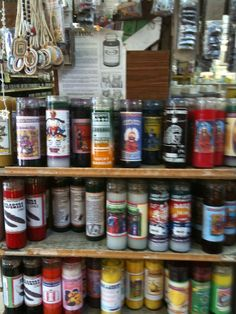 A candle shelf inside a botanica. The candles are used for a different Santeria spell—Protection, Money, Love, Go Away Evil, etc. Herbs and oils are usually sprinkled and dripped over the top of the candle to execute the spell, with each color representing a different intention.
