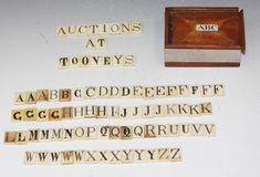 A collection of Victorian bone alphabet tiles, each with stained and incised capital letter, within original rectangular box, the sliding cover inset with a bone panel inscribed 'ABC', length approx 9cm. #tooveys