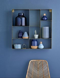 blue wall with blue vignettes on wooden shelf