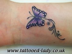 Small purple butterfly tattoo on wrist one of a cpl together, different colors