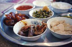 Traditional Syrian Breakfast: Jebneh (white brined cheese), Makdous (eggplant pickles), Labneh (strained yoghurt), Shanklish (herbed blue cheese), Arisheh (homemade curd cheese), Zaytoon (green olives), Khubz Arabi (pita bread), jams