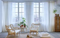 A bright living room featuring mullion windows with one layer of sheer white curtains that filters the daylight, one layer that stops reflections on screens and one layer of white thick curtains for privacy.