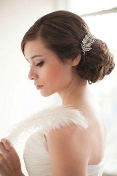 Les cheveux bruns de la mariée, sûrement d'une longueur conséquente, sont attachés en chignon bas, volumineux. La raie est sur le côté, ce qui permet à une grande mèche de revenir joliment sur le front de l'autre côté. Ici pas de plume naturelle mais une grande barrette en strass argentés. Cet accessoire retient les cheveux sur le dessus du chignon. Beau bijou ! La mariée ne porte pas d'autre bijou, et est maquillée de façon subtile. Sobre et très chic