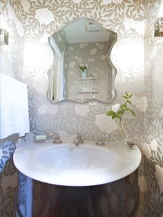 Floral-print silver wallpaper adds a glamorous touch to this small bathroom, which features a round marble sink and decorative curved wall mirror.