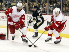 CrowdCam Hot Shot: Detroit Red Wings defenseman Kyle Quincey and defenseman Brendan Smith work together to clear the puck against the Pittsburgh Penguins during the second period at the CONSOL Energy Center. The Detroit Red Wings won 4-1. Photo by Charles LeClaire