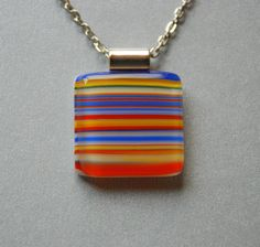 Fused Glass Pendant Necklace Blue Red Yellow and White Stripes Handmade by Penny Glass Girl. $24.00, via Etsy.