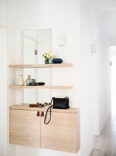 Natural wood shelves in front of a mirror