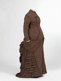 This circa 1880 maternity dress was remodeled from a wedding dress, with a bodice that closed tightly above the waist and a wide ruffled skirt.