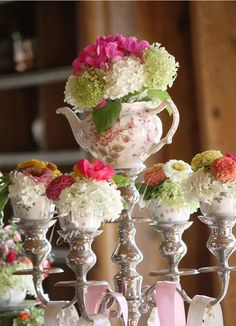 Fresh blooms in a teapot & cups decorate a silver candelabra
