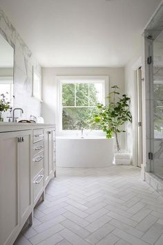 Welcoming white bathroom is fitted with honed white marble herringbone floor tiles fixed framing a white dual washstand accented with polished nickel Best Bathroom Flooring, Bathroom Floor Tiles, Kitchen Flooring, Bathroom Marble, Kitchen Countertops, Kitchen Backsplash, Mirror Bathroom, Quartz Countertops, Room Tiles