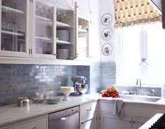 kitchen with blue gray subway tile and white cabinets