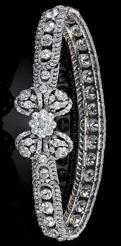 An impressive and highly important diamond ornament from the collection of the Russian Imperial Family, Russia, 2nd half of the 18th century. Consisting of an articulated band mounted in silver with a row of twenty-seven graduated cushion-shaped diamonds in open settings within a border of stylised foliate motifs close set with smaller similarly cut stones, embellished with a ribbon bow clasp close set in silver with cushion-shaped diamonds in an openwork floral and foliate pattern.