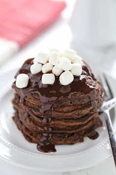 Hot Chocolate Pancakes feature rich chocolate buttermilk pancakes with a thick chocolate fudge topping and garnish with mini marshmallows.