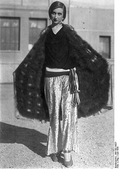 Early 1930s style- ankle length, wide legged trousers in fabulous shiny fabric, worn with low slung, tie-belt and long, quite oversized jacket. Parisian model in June, 1930, wearing 'beach suit with summer fur'. (Image source http://en.wikipedia.org/wiki/File:Bundesarchiv_Bild_102-10027,_Pariser_Modell.jpg )