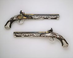 "1800-1801 British Flintlock pistols at the Metropolitan Museum of Art, New York - From the curators' comments: ""These pistols are among the finest known examples of English Neoclassical-style firearms. Each stock is inlaid with engraved sheet silver and embellished with heavy cast-silver mounts. This decoration was inspired by contemporary French Empire firearms..."""
