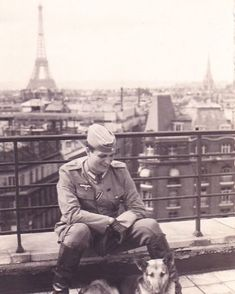 A Wehrmacht soldier with his dog, with the Eiffel Tower in the background.