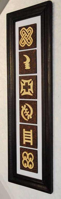 A wall hanging painting, with Adinkra symbols are presented as wooden motifs. The symbols vary in each piece. Dark wooden frames.  http://afrimood.com/products/home-decoration/symbols.html#.UKE_2I7rbHg