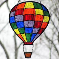 Rainbow stained glass hot air balloon suncatcher handcrafted in the Tiffany method using beautiful Waterglass textured glass made by the Spectrum Glass Company. Waterglass has a gentle texture that resembles water on a lake. The pieces have been arranged so it appears that the balloon