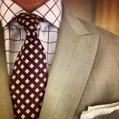 Beige jacket, white shirt with red windowpane plaid, red tie