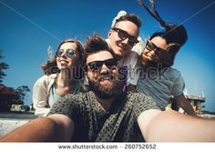 Multiracial group of young hipster friends make selfie photo with smartphone camera in Phuket while traveling across Thailand on vacation. Funny outdoor activity of young students away from home. - stock photo