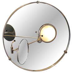 "Satellite Mirror by Eileen Gray    1960's  A ""Satellite Mirror"" by Eileen Gray,   Created for her home in the south of France, 1927.  This mirror is a later reissue by Echart International,  Circa 1960.  Nickel plated brass structure Mirror, sanded glass cover for two lamp bulbs.  The magnifying mirror is maintained by two locking handles.  The central arm rotates 360 degrees and pivots."