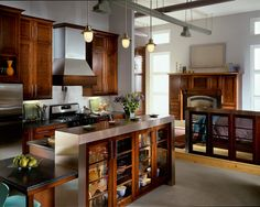 Tall wall cabinetry in warm Kaffe resembles beautiful art on studio walls and provides additional storage to a small galley kitchen.