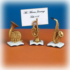 """Perfect for any music lover. Our Horn Musical Instrument Place Card Holders will make the great addition to any reception or party with a music theme. Item is sold with three different horn instruments: French Horn, Trumpet and Saxophone. Instruments all sit on a book of notes. Each instrument is made of resin and painted to look like brass. Each measure approx.: 3 1/4"""" x 1 3/4"""" and hold a 2"""" x 3"""" place card or photo.    Sold in a Set of 6  #weddingfavors"""