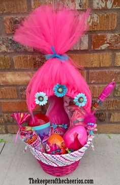 "Trolls Movie Easter Basket Idea Like most kids right now my daughter is crazy obsessed with the new Trolls Movie so for Easter this year I wanted to make her an extra special Trolls Easter basket (Poppy inspired hair). MATERIALS Basket Hot pink tulle (it takes one 6"" x 25 yard roll) Bright blue ribbon Bright blue flowers (I used paper ones found in the scrapbook section of a craft store) Piece of cardboard scissors hot glue and glue gun Green basket filler Lots of fun troll stuff DIRECTI..."