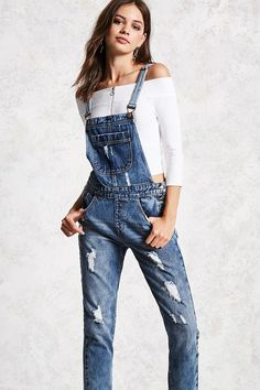 A pair of denim overalls featuring distressed details, a bib pocket, adjustable shoulder straps, a five-pocket construction, buttoned sides, and front whiskering.