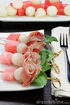 Appetizer of ham with melon and watermelon and basil on a skewer