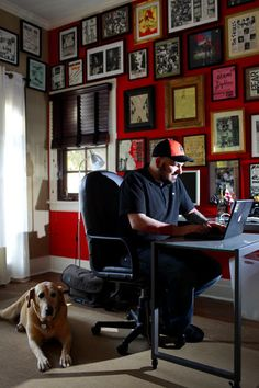 """Though he has an office for Rock Enterprises, a media agency representing street artists for advertising, book and film projects, Gastman often works in his home office. He painted one wall of the converted bedroom red to create a dramatic backdrop. """"I think about the framing, the color and and the pattern of the pieces,"""" he said of the salon-style installation. Most of the works are punk rock fliers, fanzine pages, album covers and framed letters."""