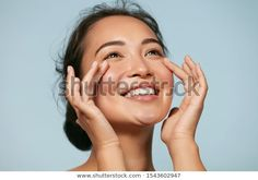 Woman with beauty face touching healthy facial skin portrait. Beautiful smiling asian girl model with natural makeup touching glowing hydrated skin on blue background closeup - Buy this stock photo and explore similar images at Adobe Stock Asian Model Girl, Girl Model, Asian Girl, Remedies For Glowing Skin, Make Funny Faces, Facial Muscles, Face Facial, Face Skin, Beauty Elixir