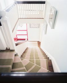 Staircase - A striped carped runner in a stairwell with light-blue walls