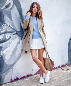 Look de tricot azul, trench coat, saia e tênis.