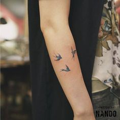 Three swallow tattoos on the right forearm.