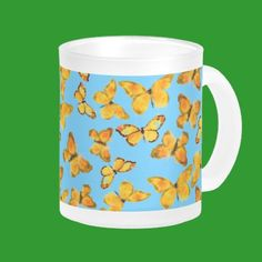 A pretty Frosted Glass Mug with a pattern of Golden Butterflies, handpainted in watercolour by Judy Adamson, on a sky blue background. This design will also fit the frosted glass Beer Mug