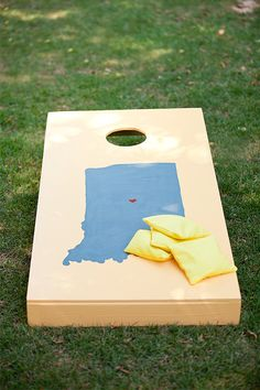 Love this, each cornhole board has the state that bride or groom is from with a heart over their city....
