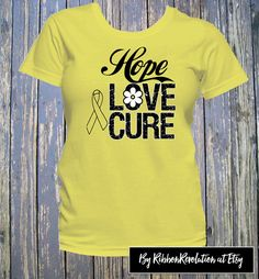 Hope Love Cure shirts with an outline ribbon signifies awareness for Adenosarcoma, Endometriosis, Ewing Sarcoma, Osteosarcoma, Sarcoma, Spina Bifida and Testicular Cancer. Design features distressed and scripted style text with an outline ribbon to highlight the color of the shirt.