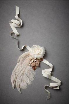 """""""Les Casquets Sash"""" byJames Coviellofor BHLDN (bhldn.com/shop). Pinned to a cream grosgrain ribbon, a vintage bloom tops a romantic-yet-moody gathering of feathers and berries. 68""""L, 1""""W ribbon; 11""""L, 5""""W embellishment. Rayon, ostrich feather, vintage silk flower, papier mâché berries. Handmade in USA. Price:$220"""