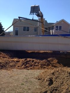 3,500 pound fiberglass pool being lowered into the ground.