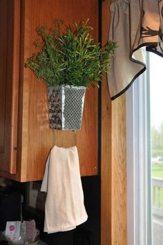 Simply turn an old cheese grater upside down, stuff it with some flowers, hang it up…and you've got a dish rag holder!
