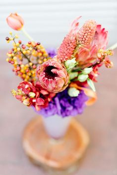 Purple and coral centerpiece with proteas and tulips | Photo by Yolande Marx | Floral design by Fleur le Cordeur