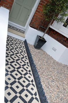 Plastered rendered front garden wall painted white metal wrought iron rail and gate victorian mosaic tile path in black and white scottish pebbles York stone balham london