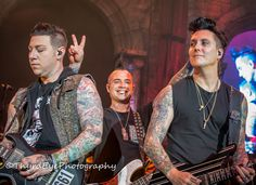Avenged Sevenfold Johnny Christ having fun with Zacky Vengeance and Synyster Gates.  Guitars, bass, tattoos, Mohawk, bunny ears, concert photography, fun, prankster, skulls, A7X