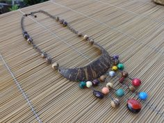 colar envelhecido,feito com corrente,sementes,contas de madeira e meia lua de coco.